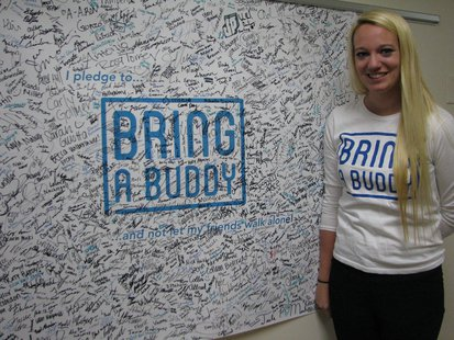 Jenna Furger with the UWSP Bring A Buddy banner, where over 1,500 students have pledged to bring a buddy instead of going out alone.