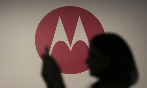 A woman takes a picture in front of a Motorola logo before the worldwide presentation of the Moto G mobile phone in Sao Paulo November 13, 2