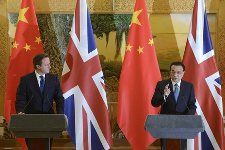 Britain's Prime Minister David Cameron (L) listens to China's Premier Li Keqiang as the two leaders deliver statements following a signing c