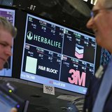 A screen displays the tickers symbols for; Herbalife, Chevron, H&R Block and 3M as traders work on the floor at the New York Stock Exchange,