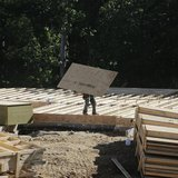 A lone carpenter carries plywood flooring at a building site of Mid-Atlantic Builders' 'The Villages of Savannah' in Brandywine, Maryland Ma