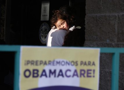 Julissa Esparza, 2, sleeps in the arms of her grandfather Leobardo Salazar, 58, as they wait in line at a health insurance enrollment event