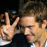"U.S. actor Paul Walker gestures to a fan during the premiere of the movie ""Fast and Furious 4"" in Taipei April 15, 2009. REUTERS/Nicky Loh"