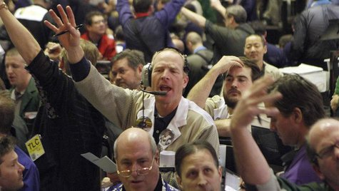 Traders in the corn options pit at the CME Group signal orders shortly before the closing bell in Chicago, in this February 11, 2011 file ph
