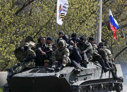 Armed men, wearing black and orange ribbons of St. George - a symbol widely associated with pro-Russian protests in Ukraine, drive an armour