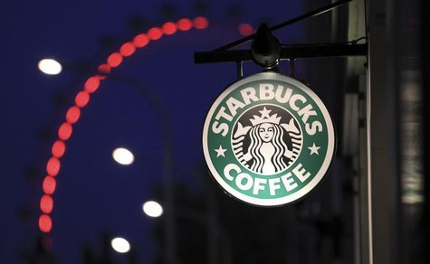 The sign outside a Starbucks coffee shop on in Westminster is seen with the London Eye in the background, in central London, December 3, 201