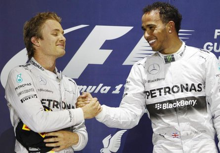 Mercedes Formula One driver Lewis Hamilton of Britain (R) is congratulated by teammate Mercedes Formula One driver Nico Rosberg of Germany o