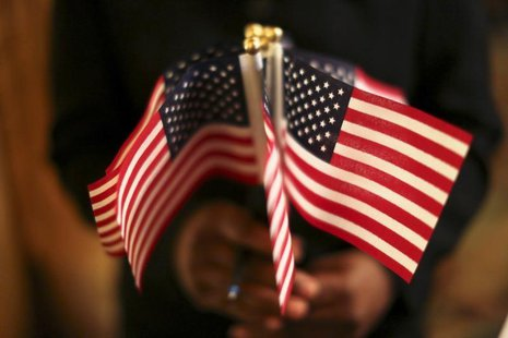 A woman holds a cluster of U.S. flags during a U.S. Citizenship and Immigration Services naturalization ceremony in Oakland, California Augu