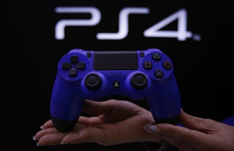 A staff at the PlayStation 4 launch event poses with the PlayStation 4's game controller before its domestic launch event at the Sony Showro