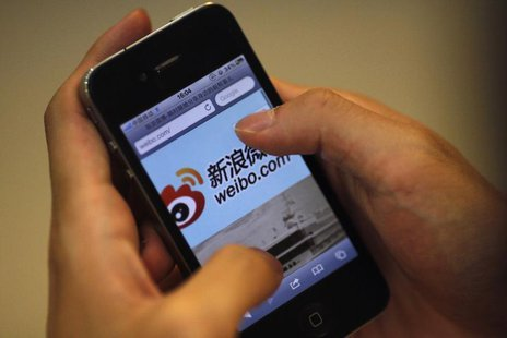 A man holds an iPhone as he visits Sina's Weibo microblogging site in Shanghai May 29, 2012. REUTERS/Carlos Barria