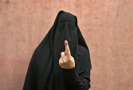 A veiled Muslim woman shows her ink-marked finger after voting outside a polling station in Doda district, north of Jammu, April 17, 2014. R