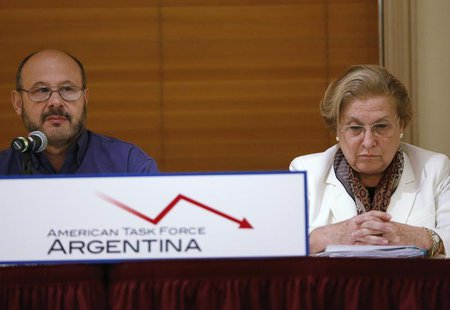Horacio Vazquez (L), 56, from Buenos Aires, speaks while Eva Geller, 66, from Uruguay, looks down with other pensioners during a news confer