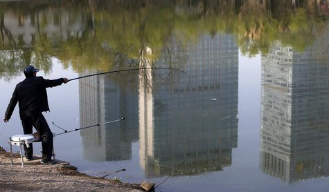 A man fishes next to a lake with the reflection of newly-built residential buildings at a park in Shenyang, Liaoning province, April 16, 201