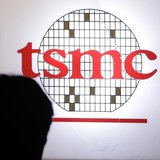 A man sits in front of the logo of Taiwan Semiconductor Manufacturing Co Ltd (TSMC) during an investors' conference in Taipei April 18, 2013