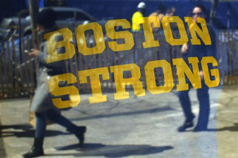 "Pedestrians are reflected in a ""Boston Strong"" t-shirt displayed in a shop window, as they walk past the site of the first bomb blast from t"