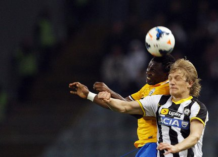 Juventus' Kwadwo Asamoah (L) jumps for the ball with Udinese's Dusan Basta during their Italian Serie A soccer match at the Friuli stadium i