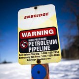 "A sign warning of a high pressure petroleum pipeline is seen on the ""Line 9"" Enbridge oil pipeline route in East Don Parkland in Toronto, Ma"