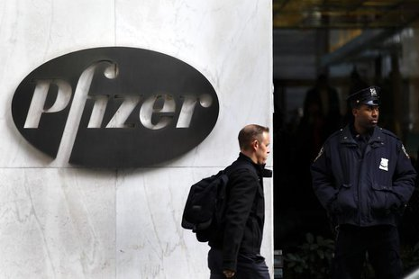 A man walks past the Pfizer logo next to a New York Police Officer standing outside Pfizer's world headquarters in New York November 5, 2013