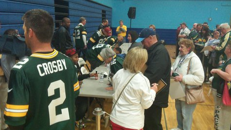 Packer CB Jarrett Bush signing autographs while Mason Crosby talks with the media