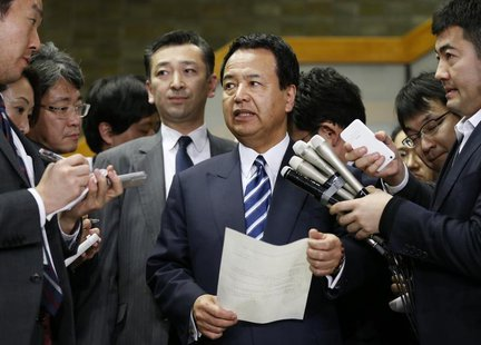 Japan's Economics Minister Akira Amari (C) speaks as he is surrounded by media after meetings with U.S. REUTERS/Issei Kato
