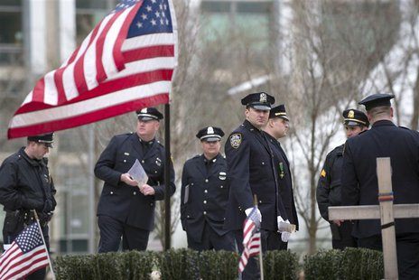 Police officers from around the state of Massachusetts gather near a makeshift memorial for slain Massachusetts Institute of Technology poli