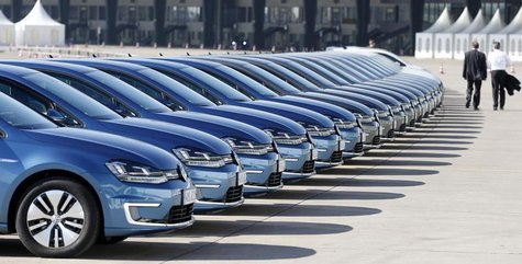 People walk past a row of Volkswagen e-Golf cars during the company's annual news conference in Berlin March 13, 2014. REUTERS/Tobias Schwar