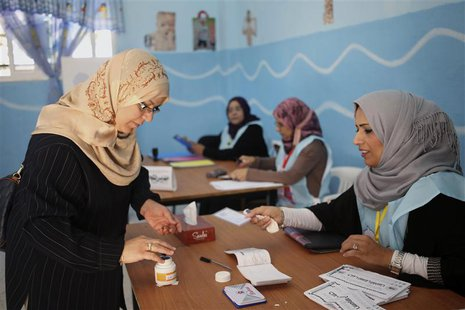 A woman dips her finger in a bottle of ink before voting in the municipal election at a polling station in Benghazi April 19, 2014. REUTERS/