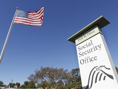 An American flag flutters in the wind next to signage for a United States Social Security Administration office in Burbank, California Octob