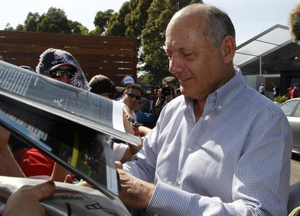 Chairman and CEO of McLaren Formula One team Ron Dennis signs autographs at the first practice session of the Australian F1 Grand Prix at th