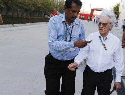 Formula One commercial supremo Bernie Ecclestone's hair blows in the wind while being interviewed as he walks at the paddock after the third