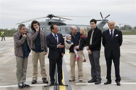 French Presidnt Francois Hollande (C) speaks with former French hostages and journalists, from L-2ndR, Didier Francois, Edouard Elias , Nico