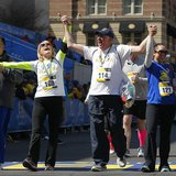 Beth (2nd L) and Michael (C) Bourgault, 2013 Boston Marathon bombing survivors, cross the marathon finish line during a Tribute Run for surv