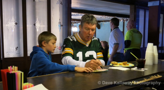 Lynn Dickey signing something for a young Packer fan at the VIP party at Club 64...