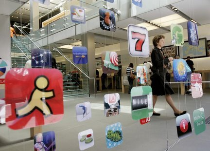 A woman walks past icons for Apple applications at the company's retail store in San Francisco, California April 22, 2009. REUTERS/Robert Ga