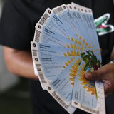 A Colombian fan displays his FIFA 2014 World Cup tickets for the match between Colombia and Greece, in Rio de Janeiro April 18, 2014. REUTER