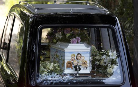 A hearse carrying the coffin of Peaches Geldof, painted with a picture of her family, arrives for her funeral service at the St Mary Magdale