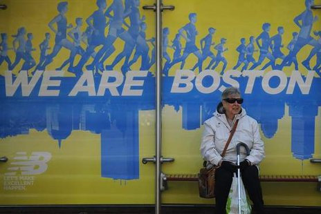 A woman waits at a bus stop near the finish line of the Boston Marathon in Boston, Massachusetts on April 17th, 2014.  (Reuters/Brian Snyder)