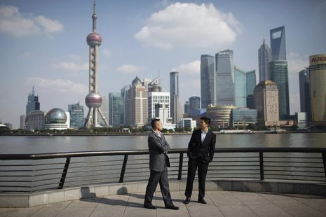 Businessmen walk on the Bund near the Huangpu River in front of the financial district of Pudong in Shanghai November 21, 2011. REUTERS/Aly