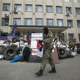 A pro-Russian armed man walks near a barricade outside a regional government building seized by them in Kramatorsk, eastern Ukraine April 22