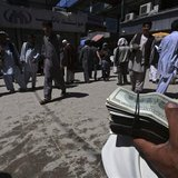 A money changer holds a stack of U.S. dollars at Kabul's largest money market April 23, 2014. REUTERS/Omar Sobhani