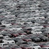 An employee yawns as he walks among General Motors' new Chinese-made cars at a parking lot in Shenyang, Liaoning province April 21, 2014. RE