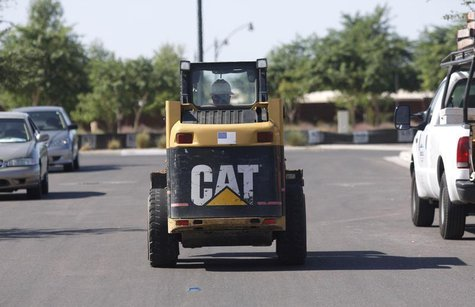 A worker drives a Caterpillar tractor near a construction site in Gilbert, Arizona October 20, 2009.REUTERS/Joshua Lott