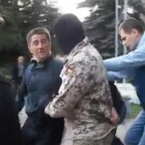 Horlivka city deputy Volodymyr Rybak (L) is manhandled by several men, among them a masked man in camouflage, outside a city hall building i