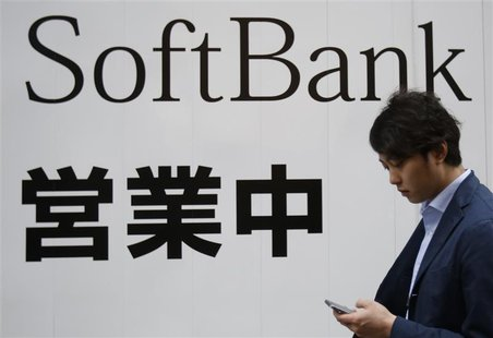 A man holding his mobile phone walks past the logo of Softbank Corp at its branch in Tokyo April 22, 2014. REUTERS/Yuya Shino