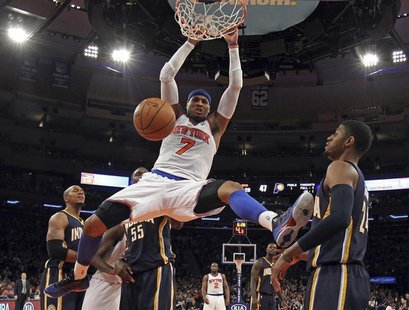 New York Knicks forward Carmelo Anthony slam dunks the ball in front of Indiana Pacers forward Paul George (R) in the second half of their N