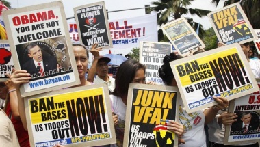 Protesters hold signs outside the U.S. Embassy in Manila in anticipation of President Obama's Asia trip.  REUTERS/Romeo Ronoco