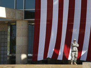 A soldier stands outside the venue for a memorial service on Sadowski Field at III Corps Headquarters for the victims of last Wednesday's sh