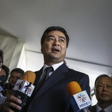Democrat Party leader and former Prime Minister Abhisit Vejjajiva speaks to reporters after reporting to the Office of the Attorney General