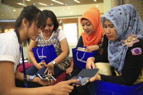 Women listen as a Samsung employee provides instructions on using their new Galaxy smartphones in Jakarta, April 11, 2014. REUTERS/Beawihart