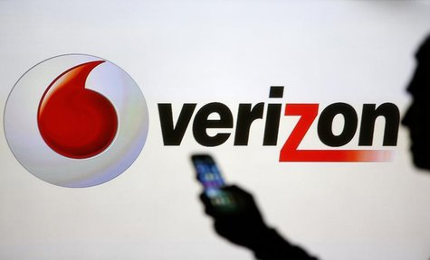 A man is silhouetted against a video screen with Vodafone and Verizon logos as he poses with a Samsung Galaxy S3 in this photo illustration